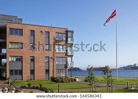 Modern five-storey house on the sea shore with Norwegian flag, Norway, sunny summer day