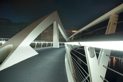 Modern footbridge over River Clyde in Glasgow, Scotland, UK, Europe. Shot from low angle at night to show illuminated handrail and geometric shapes.