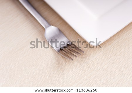 Modern fork and plate on wooden table