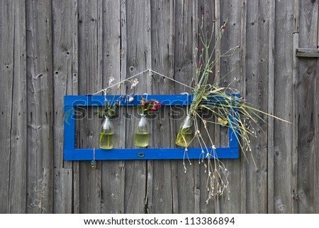 Modern frame on the old wooden wall, with flowers inside of three bottles