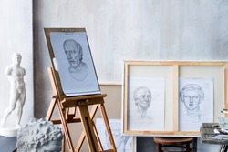 Modern freelancer artist sculptor creator art workshop workplace studio exhibition interior with pencil drawings on wooden esasel, sketches: male portrait and gypsum plaster sculptures in university