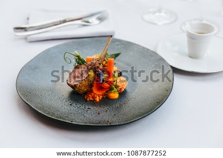Modern French cuisine: Roasted Lamb neck & rack served with carrot, yellow curry served in black stone plate with fork and knife.