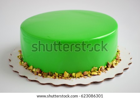 Modern French mousse cake with green mirror glaze. Picture for a menu or a confectionery catalog.