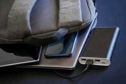 Modern gadgets - a smartphone, tablet and laptop or ultrabook - lie in a gray city backpack next to a large external battery - power bank. Charge your gadgets while traveling and trip. Close-up