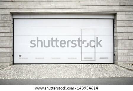 Modern garage door. Large automatic up and over garage door with inclusion of smaller personal door.