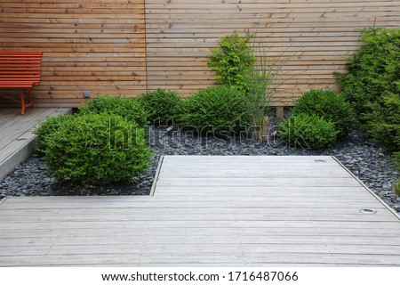 Modern garden design and terrace construction with a timber floor terrace and grass plants bush box trees in a patch with crushed stone in front of a wooden wall