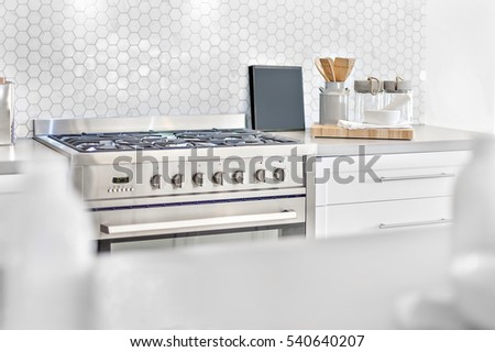 Modern gas stove top view with kitchen utensils beside bee shape wall tile, front is blurred and focus the back, very clean area also perfect lightning.