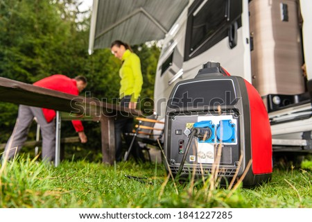 Modern Gasoline Powered Generator Running Next to Camper Van Recreational Vehicle. Powering RV Camping Pitch with Own Energy Source. Foto d'archivio ©