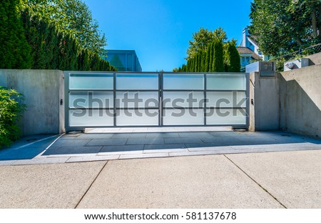 Modern gates with driveway to the luxury house.  North America.