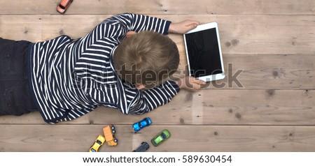 Modern generation. Kid playing on ipad