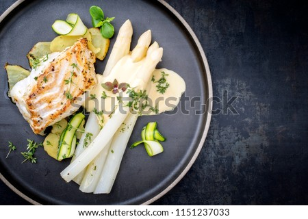 Modern German fried cod fish filet with white asparagus in hollandaise sauce with roast potatoes and sliced zucchini as top view on a plate with copy space right