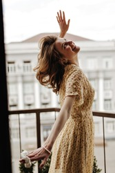 Modern girl in good mood in yellow stylish dress posing on balcony. Cheerful woman in floral summer clothes smiling on terrace..