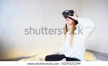 Modern girl visits different places and looks through streets of virtual reality with help of special glasses. Woman of European appearance with long blond hair virtually travels and chooses place for #1039321294