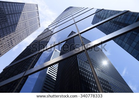 modern glass and steel office buildings in lower manhattan with blue sky #340778333