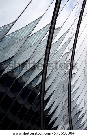Modern glass architecture combining curvilinear and angular shapes. Refined photo of hi-tech building fragment with reflections. Abstract industry or technology background #573610084