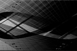 Modern glass architecture with curvilinear shapes in darkness. Grunge double exposure photo of office building fragment. Abstract image on the subject of industry or technology.