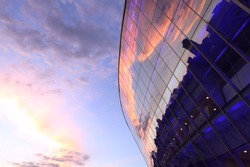 Modern glass building with reflected evening city and sunset sky in it