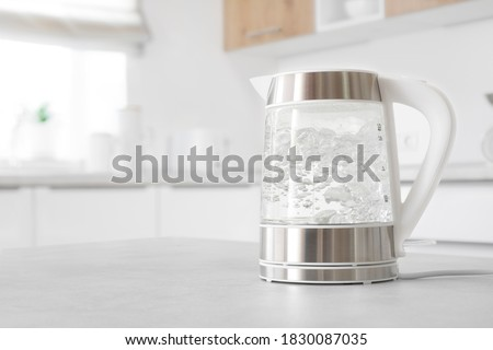 Modern glass electric kettle boiling on kitchen table Stock photo ©