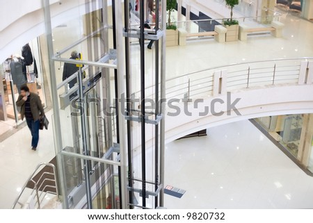 Modern glass elevator in the mall. Walking peoples in motion blur