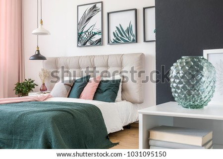 Modern, glass vase in a bedroom interior and a double bed in the background with wool blanket and colorful pillows