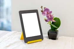 Modern gray electronic book or tablet with a blank mockup screen on a yellow stand next to an artificial pink orchid on the kitchen table with a linen tablecloth by the window