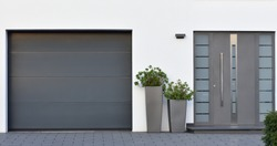 Modern gray garage, next to the Scandinavian-style house. Private garage with automatic door in a European city in Germany