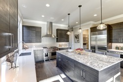Modern gray kitchen features dark gray flat front cabinets paired with white quartz countertops and a glossy gray linear tile backsplash. Bar style kitchen island with granite counter. Northwest, USA
