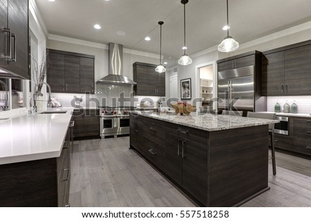 Photo of Modern gray kitchen features dark gray flat front cabinets paired with white quartz countertops and a glossy gray linear tile backsplash. Northwest, USA