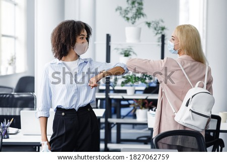 Modern greeting and new normal at social distancing. African american and european women in protective masks touching by elbows instead of shaking hands to protect against virus epidemic in office