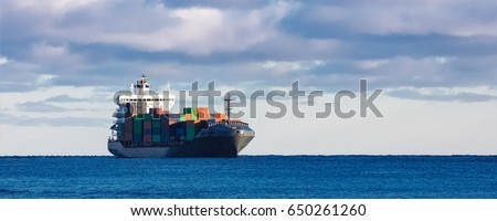 Modern grey container ship moving in still water #650261260