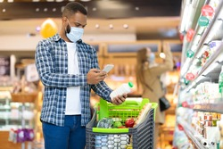 Modern Grocery Shopping. African American Man Using Mobile Phone Scanning Product With Smartphone App Standing With Trolley In Supermarket. Groceries Checklist Application. Free Space For Text