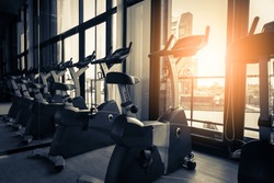Modern gym interior with equipment. Row of training exercise bikes wheel detail, backlight. Healthy lifestyle concept
