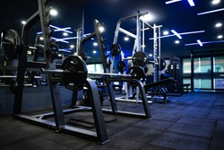 Modern gym Sports equipment in the gym Barbells of different weight on the RACK And a machine for building muscles, with blue lights interiors, gym flooring with cushioning sheets. Focusing shooting t