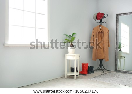 Modern hallway interior with clothes on hanger stand and mirror Foto d'archivio ©