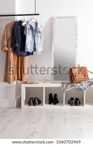 Modern hallway interior with hanging clothes and shoe rack #1060702469