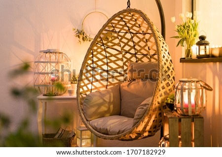 Modern hanging bamboo chair with a cosy beige pillow, candles, lanterns and flowers on a summer evening terrace Foto d'archivio ©