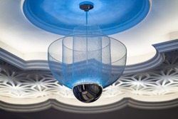 Modern hanging blue ceiling lamp with round and cylinder shaped decorated lantern on white craved ceiling with ambient led light installed.