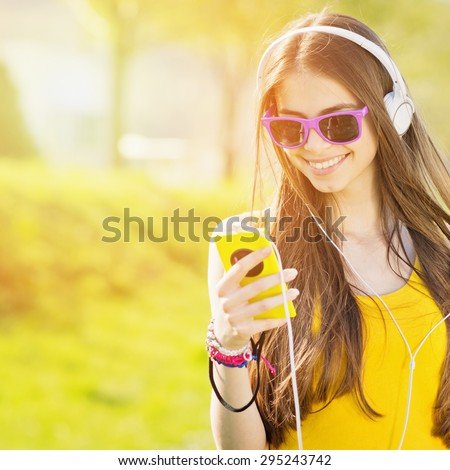 Modern happy millennial teenage girl with sunglasses, headphones and smartphone smiling standing outdoors in park on sunny summer day. Square, retouched, vibrant colors.