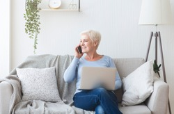 Modern happy old lady sitting on sofa at home, holding laptop and talking by phone, free space