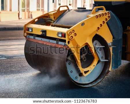 Modern heavy asphalt roller that stack and press hot asphalt. Yellow road repair machine. Repairing in modern city with vibration roller compactor #1123676783