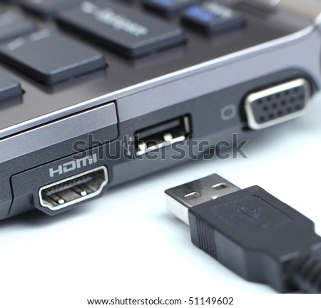 modern hi-end carbon laptop computer with great connectivity and a USB cable on white background