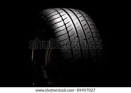 Modern high-performance sport summer tyre isolated on a black background. Horizontal composition.