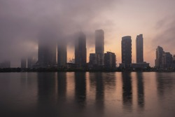 Modern high rise condo and business buildings at waterfront covered with low clouds, fog, haze, smoke at sunrise sunset hour reflecting in still water surface. Hot real estate market concept.
