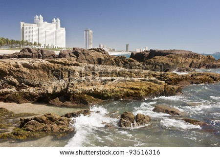Modern high-rise hotels behind seaside rocks and the Pacific Ocean