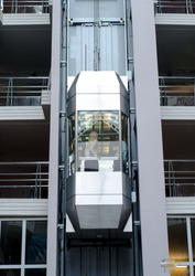 Modern high-speed metal and glass passenger elevator in an office building.