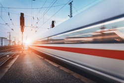 Modern high speed passenger train on railroad in motion at sunset. Blurred commuter train. Railway station at dusk with vintage toning. Travel background, railway tourism. Industrial landscape. Train