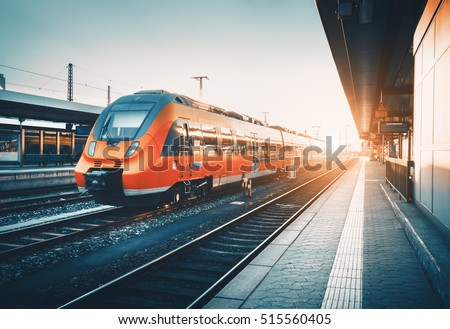 Modern high speed red commuter train at the railway station at colorful sunset. Railroad with vintage toning. Train at railway platform. Industrial landscape. Railway tourism. Vintage toning. Concept #515560405