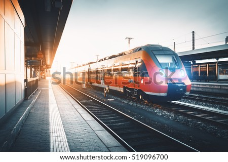 Modern high speed red commuter train at the railway station at sunset. Turning on train headlights. Railroad with vintage toning. Train at railway platform. Industrial landscape. Railway tourism #519096700