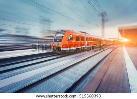 Modern high speed red passenger commuter train in motion at the railway platform at sunset. Railway station. Railroad with motion blur effect. Industrial landscape with train. Vintage toning #515560393