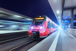 Modern high speed red passenger train moving through railway station at night. Railway station in Nuremberg. Railroad with motion blur effect. Industrial concept . Railroad travel, railway tourism.